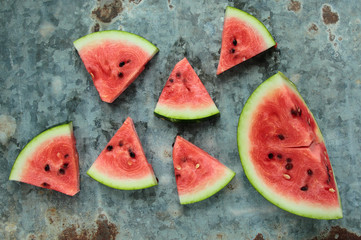 Fresh watermelon sliced in triangles on old metal board