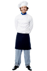 Young chef standing with hands behind