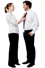 Pretty woman adjusting her husband's tie