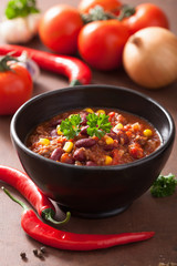 mexican chili con carne in black bowl with ingredients