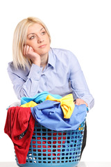 Bored woman leaning on a laundry basket