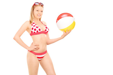 Attractive woman in bikini holding a beach ball