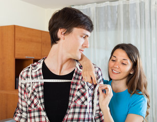 Young woman measuring  shoulders of boyfriend