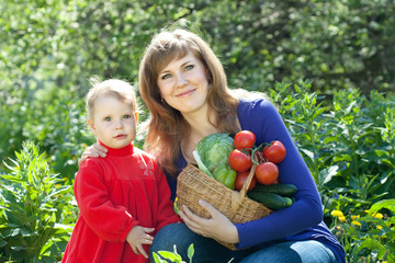 Happy woman and baby girl with vegetables