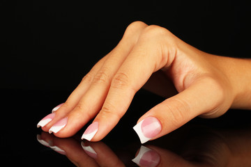 Beautiful woman's hand with french manicure on black background