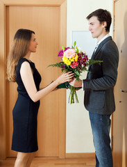 Happy wife takes bunch of flowers from her husband