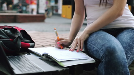 Female student doing homework with laptop and notebook in city