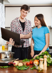 Happy  couple cooking with notebook