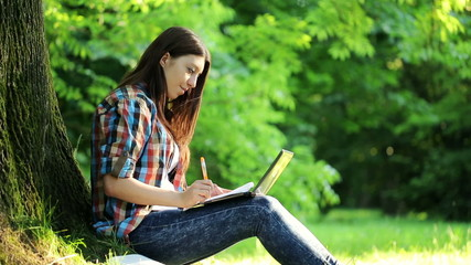 Young student doing homework with laptop and notebook in park