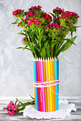 Beautiful flowers in colorful pencils vase on grey background