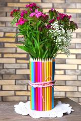 Beautiful flowers in colorful pencils vase