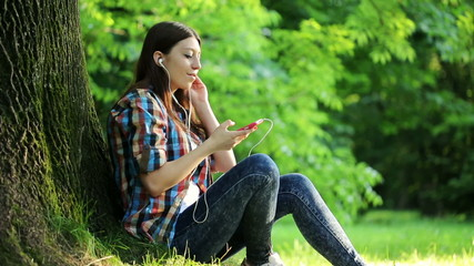 Young teenage woman listen to music on her smartphone in park