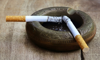 Burning cigarette on an old ashtray