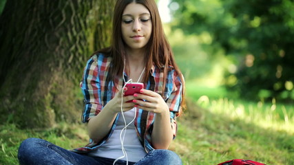 Young woman listen to music on her smartphone in park