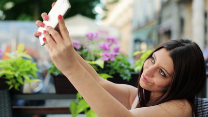 Woman taking selfie photo in cafe with smartphone