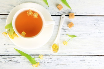 Tasty herbal tea with linden flowers on wooden table