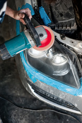 mechanic cleaning headlights with polishing power buffer machine