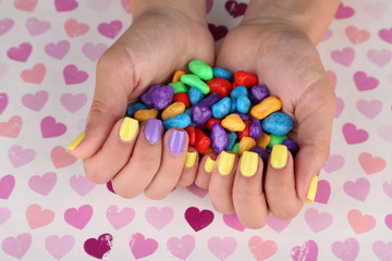 Female hand with stylish colorful nails holding colorful