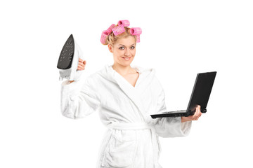 Woman in bathrobe holding an iron and a laptop