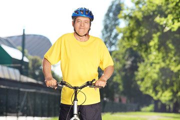 Mature male cyclist posing in a park with bike