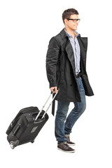 Handsome young man carrying his luggage