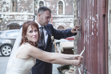 Newly wedding couple trying to open doors