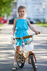Little girl standing with bicycle in park
