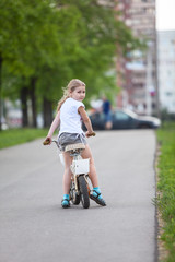 Small Caucasian girl riding a bicycle in park