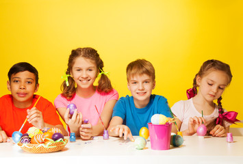 Four children colour Easter eggs at the table
