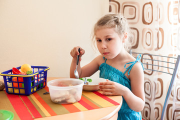 Girl in blue dress eating porridge at table and plays with toys