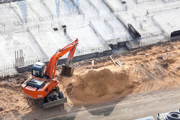 Orange excavator on foundation works