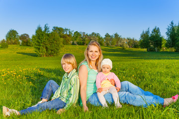 Mother with kids sits on grass in park