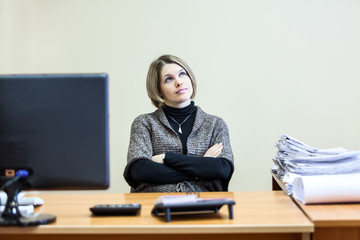 Woman with clasped hands dreaming at working place