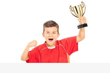 Overjoyed kid holding a trophy behind a panel