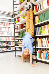 Boy standing on arms upside down leaning at shelf