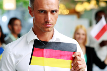 Handsome businessman holding flag of Germany