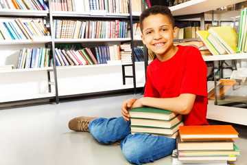 Smiling schoolchild with pile of books on floor