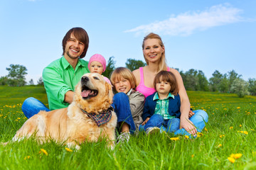 Happy family sitting on green grass with dog