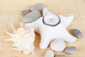 Candle in starfish with decor on bamboo napkin close-up