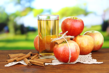 Ripe apples with with cinnamon sticks and glass of  apple drink