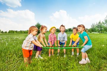 Smiling children holding one hoop together