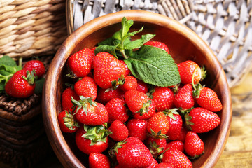 Ripe sweet strawberries in wooden bowl