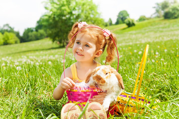 Looking girl with cute rabbit and baskets in park