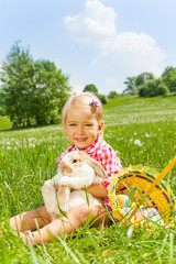Smiling small girl cuddles rabbit in green meadow