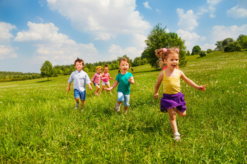 Running children in green field during summer