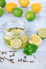 Pickled limes and cloves in glass jar,