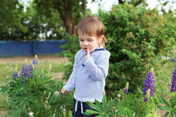 thoughtful baby standing against flowers