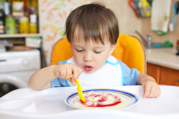 baby eating semolina porridge with jam