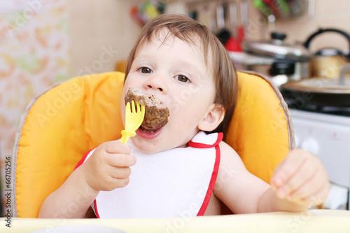 Leinwanddruck Bild baby age of 20 months eating