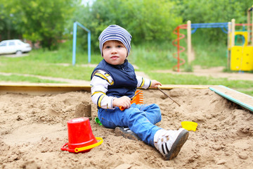baby playing with sand on playground in summer